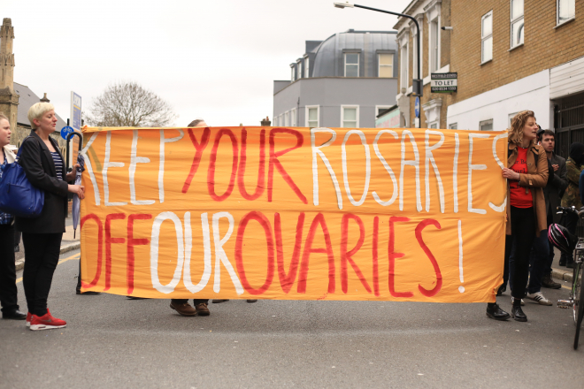 "Banner reading ""Keep your rosaries off our ovaries!"""