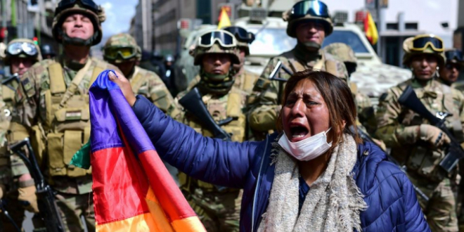 A crying woman with a face mask and flag, plus military in the background