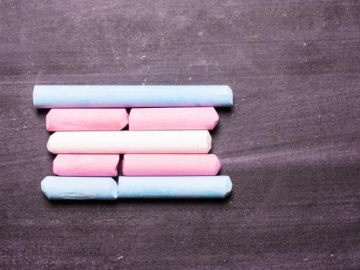 A photo of the transgender pride flag made up of pieces of chalk.