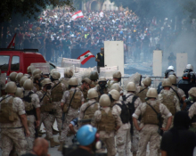 A photograph of a mass protest confronting a group of soldiers. A man in the centre waves a Lebanese flag.