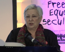 "Marieme Helie Lucas, giving a lecture in front of a sign reading ""Freedom, equality, secularism."""