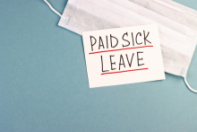 "A surgical mask with a label reading ""Paid Sick Leave"""