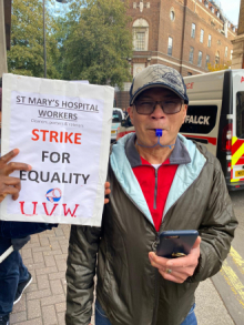 "A placard reads ""St Mary's Hospital Workers Strike for Equality. UVW"""