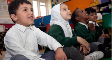 Photo of a girl wearing a hijab in primary school, alongside classmates
