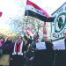 Stop the war protest with the flag of the Syrian government